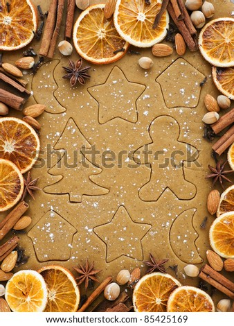 Christmas baking background dough, cookie cutters, spices and nuts. Viewed from above. - stock photo