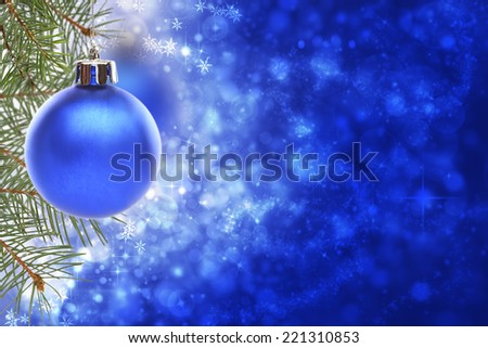 Christmas ball and spruce branches on a blurred blue shiny and sparkling background. - stock photo