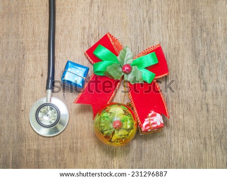 Christmas ball and Stethoscope on wooden background - stock photo