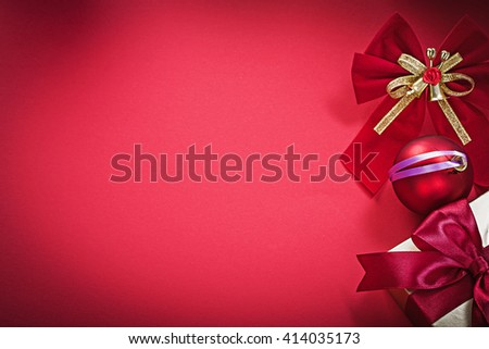 Christmas ball bow present box on red background holidays concept. - stock photo