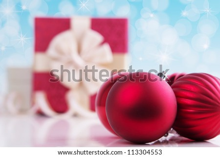 Christmas ball on abstract light background with gift box - stock photo