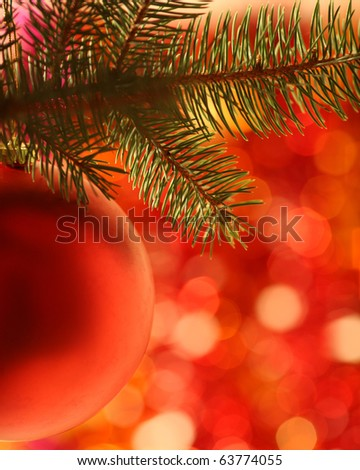 Christmas ball on fir-tree against red blurred background - stock photo