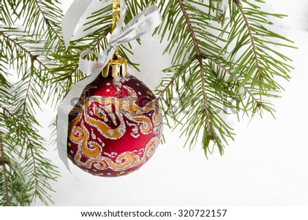 Christmas ball on snowy fir tree - stock photo