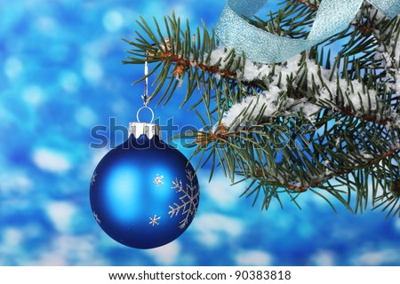 Christmas ball on the tree on blue - stock photo