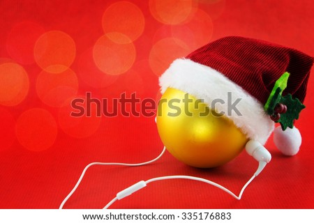 Christmas ball with Santa's hat and earphones, on red with bokeh lights - stock photo