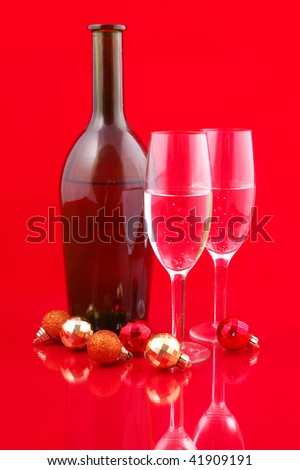 Christmas balls and champagne on red background - stock photo