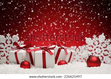 Christmas balls and gift boxes on snow over red background - stock photo