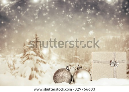 Christmas balls and gift in the snow, snowy pine trees in the background  - stock photo