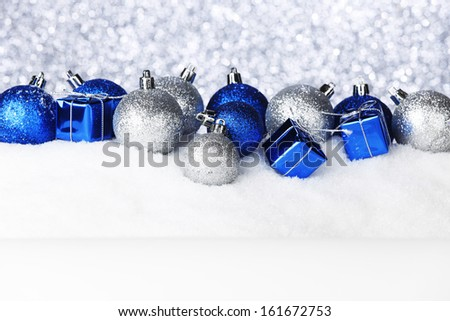 Christmas balls and gifts on snow - stock photo
