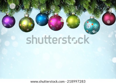Christmas balls hanging on snowy fir tree - stock photo