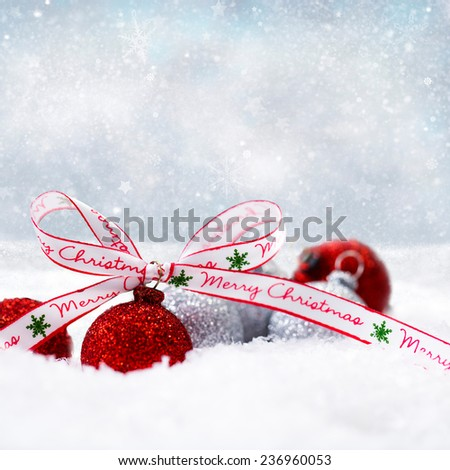 christmas balls in the snow with a merry christmas bow - stock photo