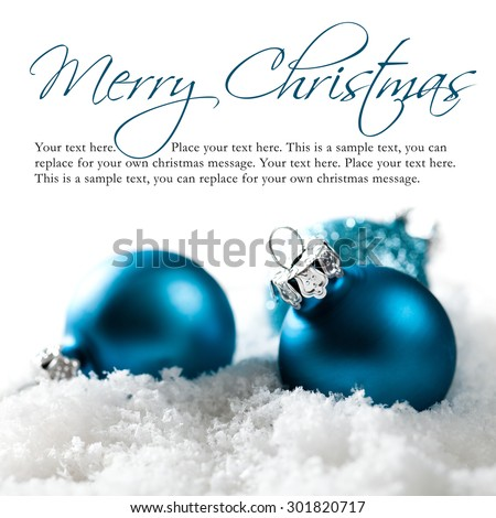 christmas balls in the snow with merry christmas greeting and sample text - stock photo