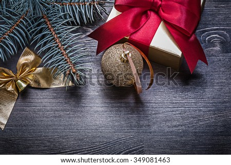 Christmas bauble bow pine branch gift box on wood board. - stock photo