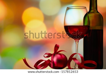 christmas bauble with red wine against colorful bokeh lights background - stock photo