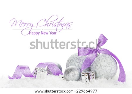 Christmas baubles and purple ribbon over snow. Isolated on white background with copy space - stock photo