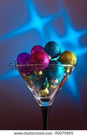 christmas baubles in wineglass on a blue background. - stock photo