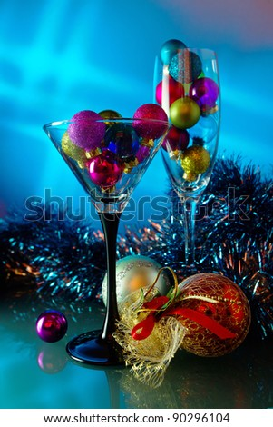 christmas baubles in wineglasses on a blue background. - stock photo