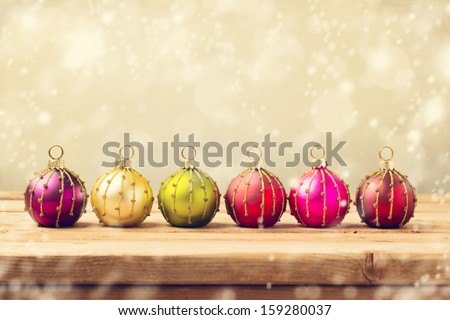Christmas baubles on wooden table over golden bokeh background - stock photo