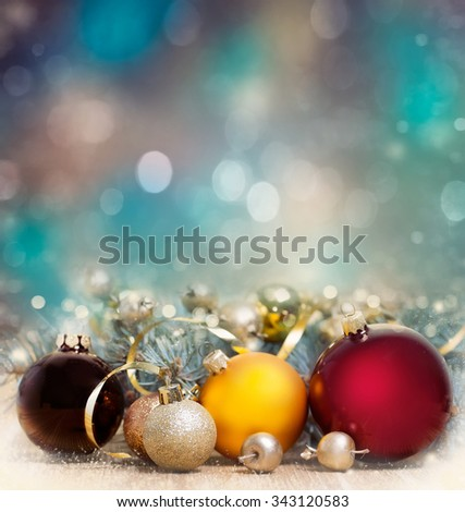 Christmas baubles with fir branch on shiny blur background. - stock photo