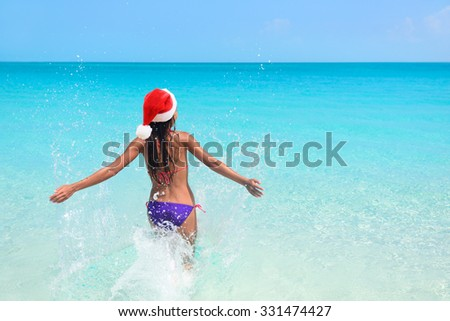 Christmas beach bikini woman swimming in ocean. Beautiful adult entering perfect turquoise water with arms back in freedom feeling free enjoying winter vacations wearing a santa hat for the holidays. - stock photo