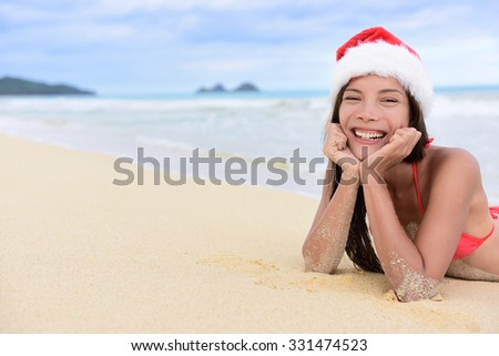 Christmas beach vacation - cute mixed race Asian Chinese girl portrait in Santa hat lying down relaxing posing on white sand in a tropical destination during winter holidays. - stock photo