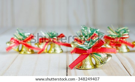Christmas bell with a red bow on wooden - stock photo