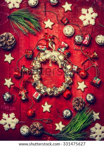 Christmas bell wreath , decorations, snowflakes and fir branches on red wooden background, top view - stock photo