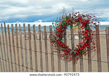 christmas berry wreath with sand dollar and starfish on beach fence - stock photo