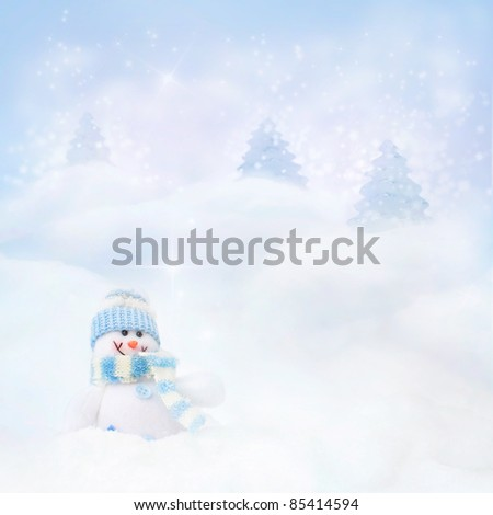 Christmas blue background. Snowman toy on the bokeh winter background in the snow and magical forest with Christmas shiny trees. - stock photo