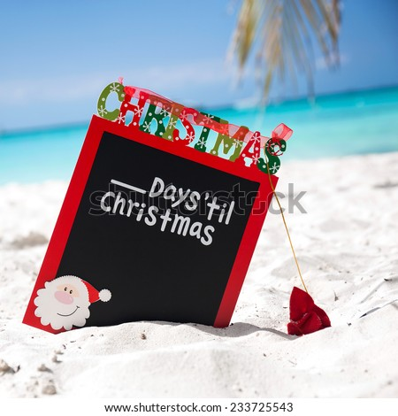 Christmas board on white sandy beach, with inscription - One day till Christmas, Tourism concept - stock photo