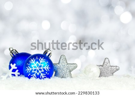 Christmas border of blue and silver ornaments in snow with twinkling light background - stock photo