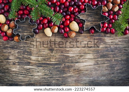 Christmas border with cranberries, spruce branch and cookie cutter on the wooden background. - stock photo