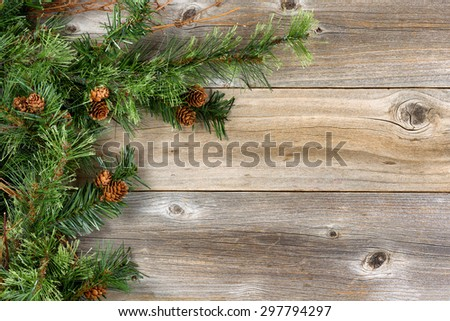 Christmas border with rough evergreen fir branches and cones on rustic wooden boards. Layout in horizontal format.   - stock photo