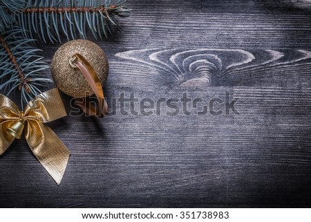 Christmas bow fir branch bauble on wooden board holiday concept. - stock photo