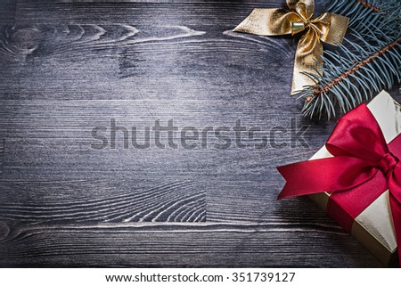 Christmas bow pine branch giftbox on wooden board holiday concept. - stock photo