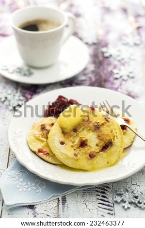Christmas breakfast - pancakes with cranberries and butter - stock photo