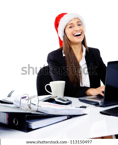 Christmas business woman celebrating the end of work year with a xmas hat at the office - stock photo