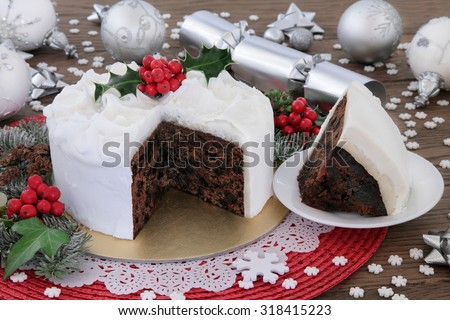 Christmas cake and slice with holly, bauble decorations and winter greenery over oak background. - stock photo
