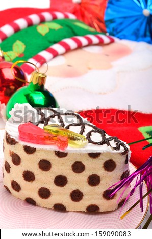 Christmas cake, christmas baubles and  Santa Claus oven glove - stock photo