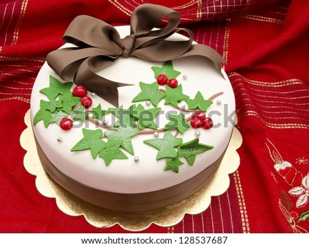 Christmas cake decorated with fondant holly leaves - stock photo