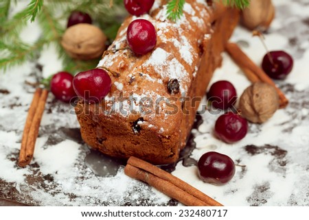 Christmas cake with raisins and cherries homemade sweet pastries powdered sugar selective focus blurred soft toned photo - stock photo