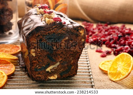 Christmas cake with with dried plums and chocolate icing on wooden background - stock photo