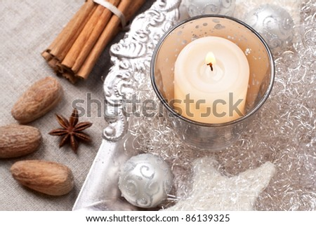 Christmas candle, baubles and other decorations with spices, still life - stock photo