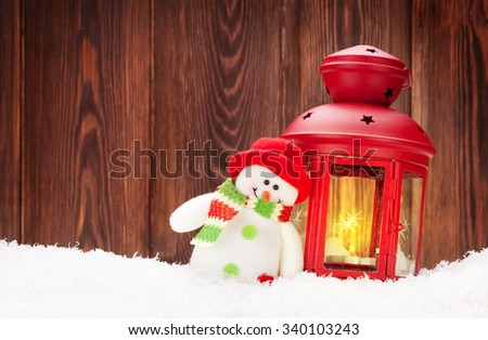 Christmas candle lantern and snowman toy in snow - stock photo