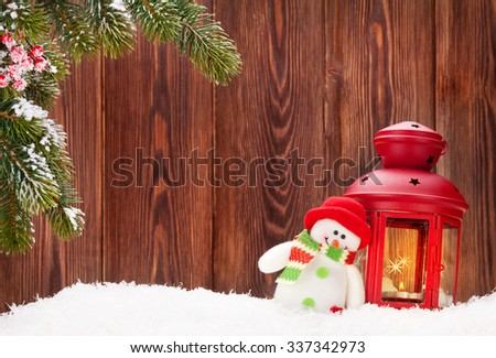 Christmas candle lantern and snowman toy in snow. View with copy space - stock photo