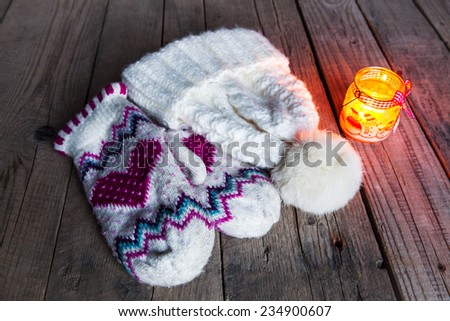Christmas candle on vintage wooden background. Snowmen and beautiful ribbon. festive decorations. Classic knitted set of mittens and hats - stock photo