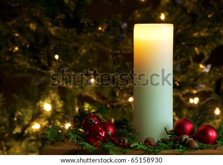 Christmas candle  with beads, Christmas balls and cedar sprigs and acorns with sparkling lights on the Christmas tree in the background. - stock photo