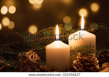 Christmas candles and ornaments over dark background with lights - stock photo
