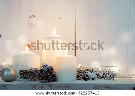Christmas candles and snowy fir branches over white wooden background with lights - stock photo