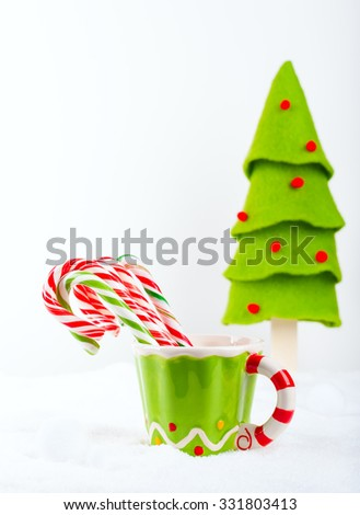 Christmas candy cane in the cup on the snow - stock photo